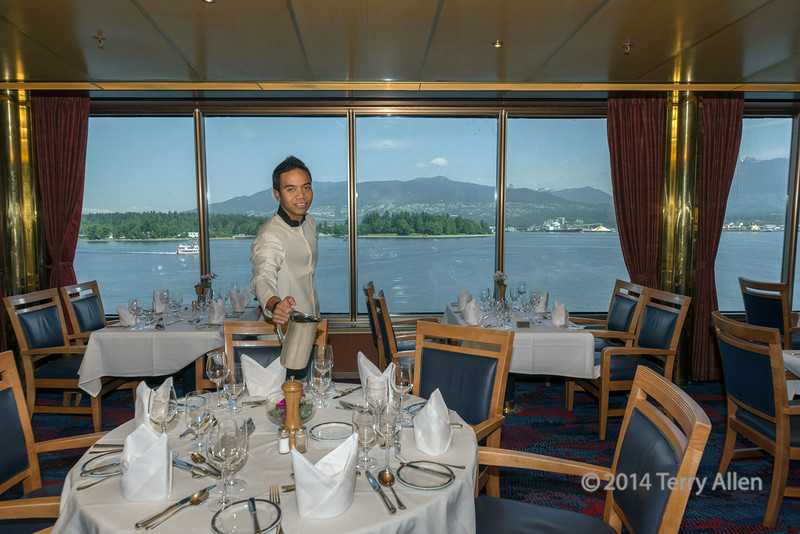 MS Statendam dining room, ready for the VSO lunch, Vancouver, BC.  The harbour and the north shore mountains can be seen out of the windows.
