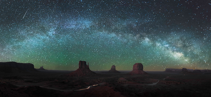 The Milky Way stretches across the night sky above Monument Valley in Arizona.