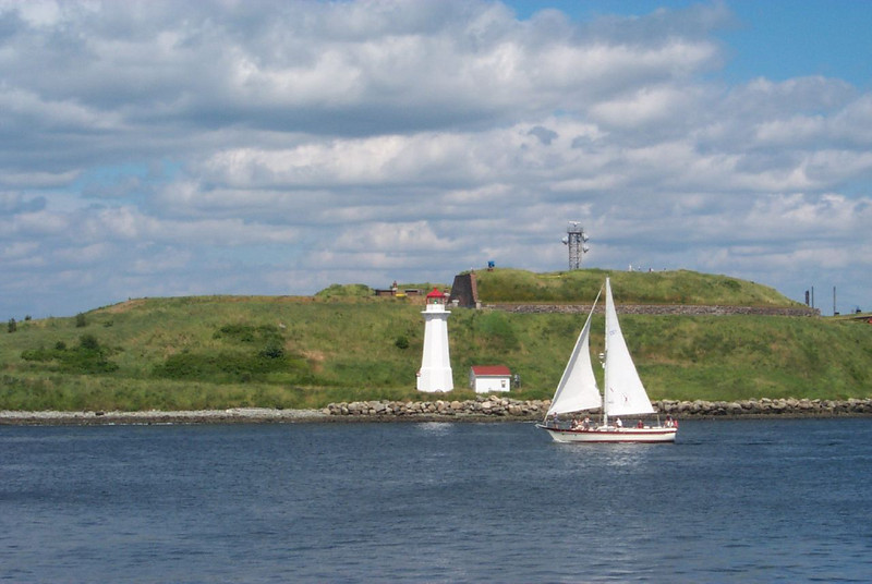 Sail boat passing by the lighthouse in George's Island, Halifax, Nova Scotia