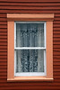 Window with lace curtain, historic ghost town of Ile aux Marins near the French owned island of Saint-Pierre off the southern coast of Newfoundland.