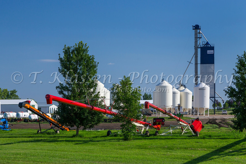 Farm implements and grain bins at Washburn, North Dakota, USA.