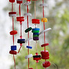 Brightly coloured plastic bottle tops threaded onto raffia to create a curtain or mobile