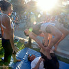Maria Corrales gives Danielle Astengo tips on how to balance atop Jason Altheide's limbs at the Thursday Night Market on July 24, 2014, in Chico, California. The three are part of the group Chico Acro. Dan Reidel — Enterprise-Record