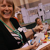 Jessica Nipp Hacker, ELCA Malaria Campaign Coordinator, shows Lynn Albers, Raleigh, N.C., and other participants how to make mixed-media paper dolls that tell something about the lives of people around the world helped by ELCA World Hunger and ELCA Malaria Campaign efforts. EH.
