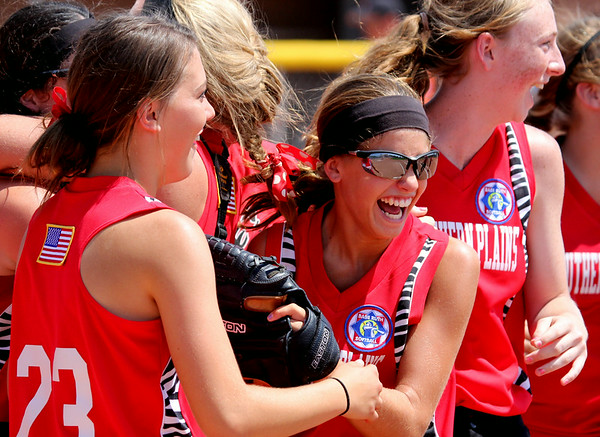 Southern Plains players Kelcy Wollert (#23), Hadlie Rittgers (center), and Macy Kennedy celebrate after upsetting defending champion Lamar, 7-6, to capture the championship on Sunday in the 2014 Babe Ruth Midwest Plains Regional Tournament. Southern Plains now advances to the 16U World Series that runs July 30 thru August 5 in Pittsfield, Mass.