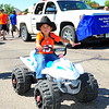 A youngster on his toy four wheeler makes his way down the parade route during the 2014 Sand & Sage Parade on Saturday, Aug. 9.