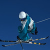 A ski jumper in mid air looks down at the ground way below. Captured against a clear blue sky, and trailing snow.