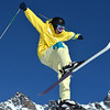 a young ski jumper having fun with a jump against a beautiful blue sky with arms spread wide, and skis akimbo