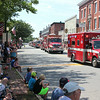 The town's fire trucks lead the way, sirens blaring, at the start of the parade down Main Street.