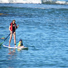 woman paddle boarding in lagoon in front of Aulani Disney Resort, Oahu, Hawaii