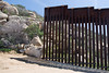 An abrupt end to the US-Mexican International Border fence where the boundary line bumps against the rocky terrain of the Jacumba Mountains in Jacuma, California. The large boulder presents little challenge to anyone inclined to step around the fence.