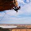 A woman rock climbing at Mt Arapiles, Victoria, Australia on a sunny day