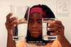 Fig 6.8 / Piaget's Conservation Task.   Choice 6 of 8  Black girl with braided hair tries to decide which of 2 different sized glasses containing same amount of water has more during Piaget's volume conservation test