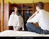m278, TA11.15 Man or woman looking into a closet and talking to his/or spouse nearby, What am I going to wear tonite?<br /> Choice 4 of 8<br /> <br /> BYARYR caucasian couple getting dressed in the morning, with woman choosing shirt. Horizontal shape, front view, three quarter length
