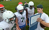 Assisant coach Matt Pasquale goes over plays with Pennridge players at practice.   Tuesday, August 12, 2014.   Photo by Geoff Patton