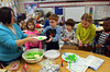 Teacher Danielle Scheer serves green eggs and ham to her first grade students at Montgomery Elementary School.  The colorful snack  was served as part of Reading Week activity held annually to celebrate Dr. Seuss's birthday.   Friday, March 7, 2014.   Photo by Geoff Patton
