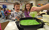 Justin Smilowitz, left, and Hailey Merritt watch as first grade teacher Danielle Scheer pours green scambled eggs into a pan at Montgomery Elementary School.   The green eggs and ham were served as part of Reading Week activity held annually to celebrate Dr. Seuss's birthday.   Friday, March 7, 2014.   Photo by Geoff Patton