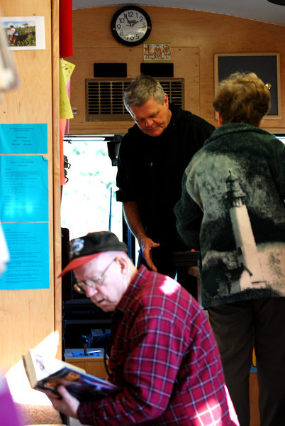 José Quezada/For the Times-Standard<br /> <br /> It is a crowded moment inside the Humboldt County Library bookmobile last Wednesday as Jack Faulkner, kneeling, and Janis Saunders conduct their library business with bookmobile librarian Ed Munn, standing in the background.