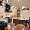 Traditional style white kitchen with kitchen island, dining area, black hood and stove, tiled backsplash, recessed lighting, lots of cabinet space, tiled floor, and warm tones.