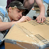 John Cross Dakota Meadows eighth graders Cain Sims (left) and Chandler Klooster tend to details on the cardboard boat they constructed as part of a team-building exercise Wednesday at Gustavus Adolphus College.