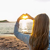 Girl holding hands in heart shape at beach