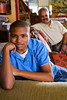 TA12.20  Choice 11 of 12  Florida, USA --- African American teenage boy sitting on couch, father in background --- Image by © Kai Chiang/Golden Pixels LLC/Corbis