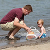 Austin Tucker with his son Shane (15 months) share a basket of toys on the beach in Vermilion on Labor Day. photo by Ray Riedel