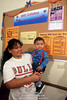 TA4.6 / WIC Photo  Choice 8 of 9  Poor Hispanic mother  standing next to bulletin board holds her toddler son at Woman Infant Care center