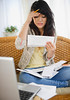 TA10.1 / Ethnic minority in a natural stressful situation<br /> <br /> Choice 10 of 14<br /> <br /> <br /> Jersey City, New Jersey, USA --- Frustrated Pacific Islander woman paying bills --- Image by © JGI/Jamie Grill/Blend Images/Corbis