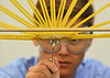Germantown Academy student A.J. Abrebaya concentrates as he prepares to attach weights  to determind the load capacity of a bridge made of uncooked spaghetti he helped design and build with teammates during the spaghetti bridge building competition held at Montgomery County Community College.   17 students from area high schools enrolled the engineering and design program developed by Johns Hopkins University.    Thursday,  July 24, 2014.   PHoto by Geoff Patton