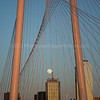 Sunset view of full moon rising over downtown Dallas, Texas, through Margaret Hunt Hill Bridge.