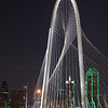 Dallas skyline behind night shot of Margaret Hunt Hill Bridge.