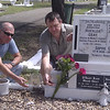 Simon and Michael scattering soil carried from Mt. Superbus on Mafalda Gray's grave at Townsville Cemetery.