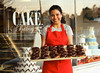 P2.5 Business Owner to replace photo on page 35 of 9th edition<br /> Choice 3 of 10<br /> <br /> 20 Nov 2009, Richmond, Virgina, USA --- Hispanic woman holding tray of doughnuts --- Image by © Ariel Skelley/Blend Images/Corbis