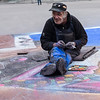 Taking a break in the middle of his chalk artwork
