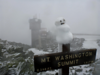 Lil snowman on the summit sign from a summer snow storm.