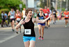 A runner waves to a spectator  at the Tex Mex 5K Race for Open Space.   Wednesday, June 25, 2014.  Photo by Geoff Pattona