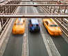 Two New York city taxis speeding across the Brooklyn Bridge surround a small blue car. Note that the cars show motion blur.