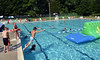 Youngsters jump in the water at the Nor Gwyn pool in Upper Gwynedd to take their turn on the Wibit, right, an inflatable floating obstacle course.  Thursday, July 10, 2014.  Photo by Geoff Patton