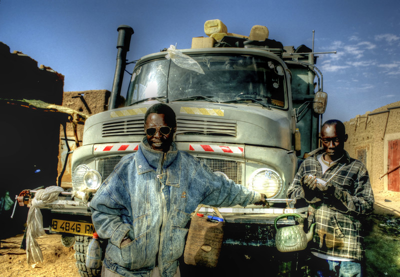 Proud truck drivers pose in front of the Mercedes Benz before crossing the Sahara desert on their way to Libya