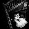 Bride and groom cuddling up by the staircase at Woodlands Hotel in Cobham
