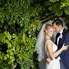 Lovely embrace of a bride and groom amongst some foliage at Northbrook Park in Farnham