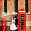 Bride and groom standing next to a post box and telephone box in Leamington Spa