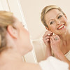 Bride adjusting her earrings in the mirror whilst getting ready for her wedding