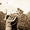 Bride and groom sharing an umbrella in the rain at The Grange in Beddington
