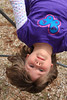 Five year old girl hanging upside down at playground.