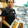 J-Mag/T. Rob Brown<br /> Jacqueline Hackett, co-owner of Hackett Hot Wings, holds the restaurant's famous Caribbean Jerk dry rub (left) with like-seasons veggies and Hot & Honey wings (right) Wednesday afternoon, July 3, 2013.