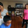 Toeur Pin of Lowell, left rear, with her daughter Selena Ou, 14, and sons Brandon Ou, 10, and George Ou, 5, in their new home at 22 Astor Street. They were displaced by the Branch Street fire. (SUN/Julia Malakie)