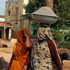 Covered Women Carrying Cement on Her Head