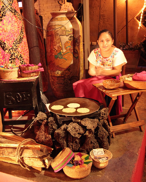 A Mexican girl, in traditional dress, hand making and cooking tortillas, in Playa Del Carmen, Mexico